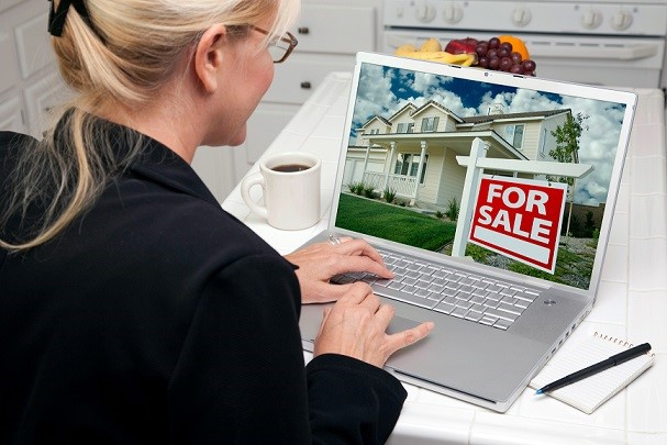 Woman In Kitchen Using Laptop to Research Real Estate. Screen can be easily used for your own message or picture. Picture on screen is my copyright as well.